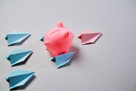 Growth, finance, investment, development and stock market concept. Pink pig soaring up on the wings of paper airplanes
