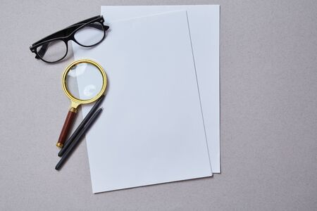 Magnifying glass lying on the paper. Analysis and analytic concept. Copy space. Mockup Reklamní fotografie
