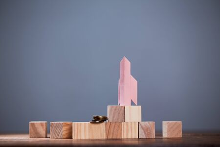 Earning, investment, startup and stock market concept. Rocket and coins, standing on cubes of wood for inscription