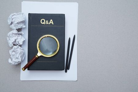 FAQ, Q and A and SEO idea. Question and answer or analysis concept. Magnifying glass, book and crumpled paper. Reklamní fotografie