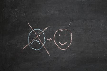 Positive thinking or Attitude and Happy Concept. Hand Drawn A Smiley Face And Sad Emotion on blackboard.