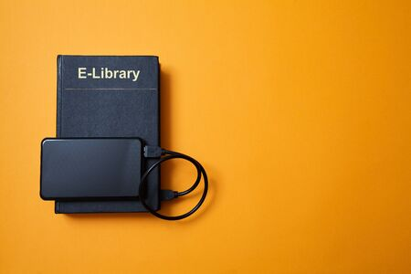 E-library. E-learning, online education or e-book. Webinar, internet courses. Book and hard drive on yellow background.