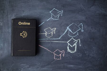 E-learning and online education or web lesson. E-library and e-book. Book on blackboard and graduate cap.