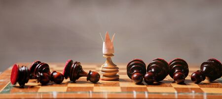 King or boss, leadership and business strategy. Board game. A pawn with a crown in the middle of the losing pieces 写真素材
