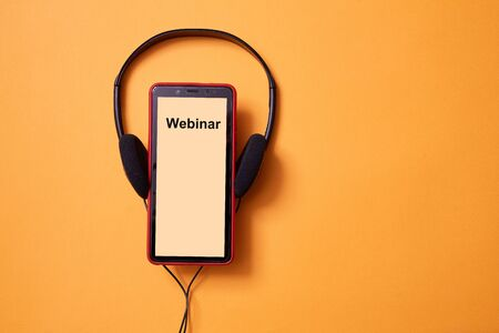 E-learning and online education concept. Webinar, internet lesson and courses. Headphones and smartphone. Copy space 写真素材