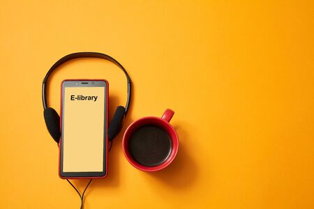 E-learning or online education concept. Webinar, internet lesson or courses. Headphones, coffee cup on yellow background.