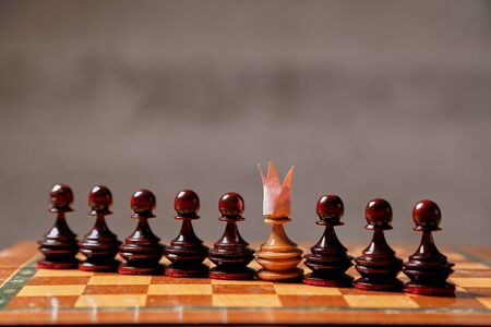 Business game, teamwork, leader and competition concept. A chess pawn with a crown on its head.