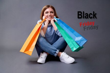 Black Friday, Shopping and commerce concept. Portrait of girl with bag sitting on the floor.