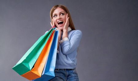 Sale, shopping, discount and Black Friday concept. Emotional girl with colored bags standing on a gray background. 写真素材