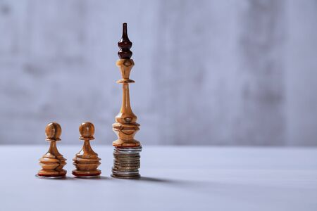 Leader, growth, finance and nvestment, development and stock market concept. Chess king on a stack of coins and pawns.
