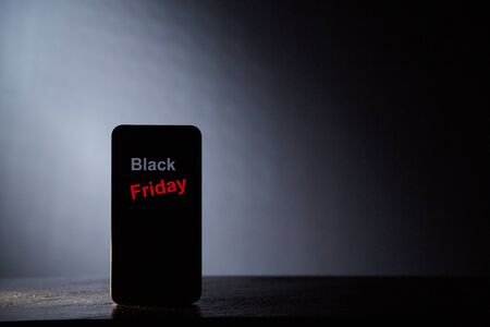 Black friday. Sale, shopping, discount and consumer society concept. Silhouette of the phone on a gray background