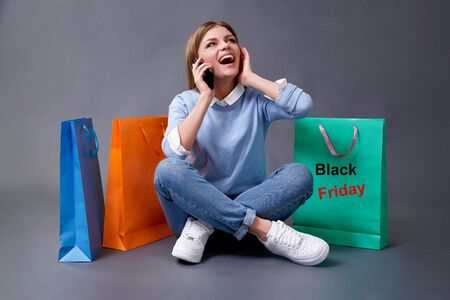 Black Friday, Shopping and commerce concept. Sake and discount. Young woman with colored bags for shopping 写真素材