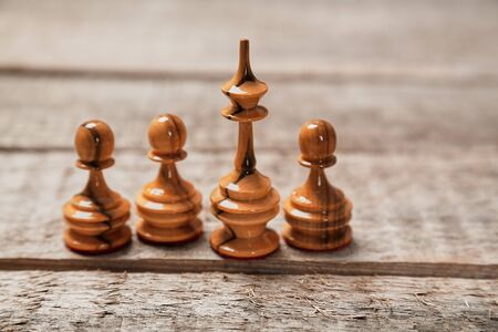 Chess game, leadership and competition concept. Winner and leader. Chess king in a paper crown. Investment concept