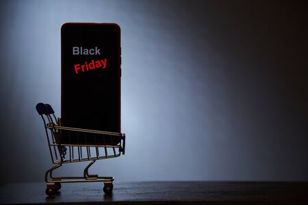 Black Friday, online shopping and sale concept. Supermarket and discount. Smartphone in shopping cart