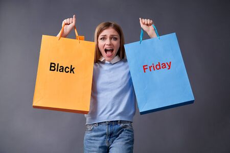 Emotional girl with colored bags standing on a gray background. Sale, shopping, discount concept. Black friday.