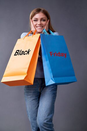 Black Friday, Shopping and commerce concept. Sake and discount. Woman with bags standing on a gray background.