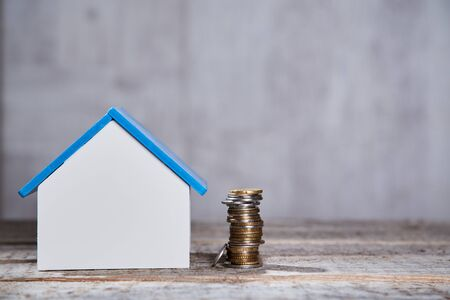 Housing structure market and investment in real estate. House mockup and pile of coins, selling and buying property Imagens