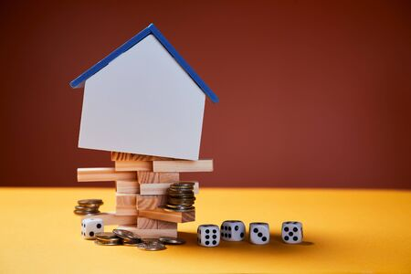 Real estate investment, success and risks at buying immovable property. House mockup with copy space, coins, game dice
