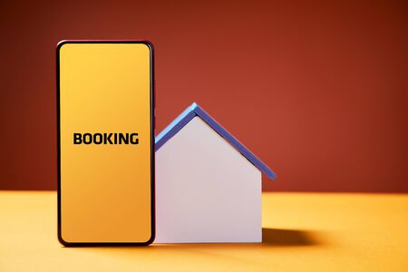 Booking vacation house. Online reservation in advance via smartphone app. House mockup with copy space. Technology and travelling concept. Red and yellow background. Banque d'images