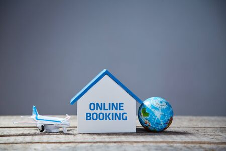 Online booking accommodation. Reservation tickets in advance. House rent. Worldwide trip. Vacation and travelling concept. Air transportation. Earth globe. Grey background.