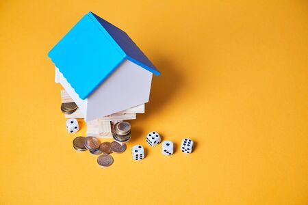 Real estate market risks and chances. Property investment and business development. House blank mockup, coins and dice Imagens