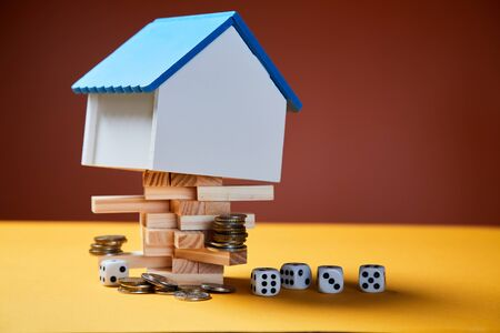 Property investment risks and opportunities. Real estate funding and development, blank house with game dice and coins