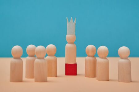 Teamwork rivalry. Team competitions. Business competitiveness. Winner, boss figure in crown stands on red wooden cube