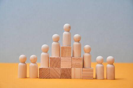Recursos humanos, gestión del talento, contratación de empleados, líder de equipo empresarial exitoso. Figuras en pirámide de madera