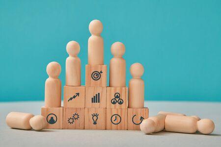 Hierarchisches System. Führung und Teamarbeit. Befehlskette. Mannschaftswettbewerb. Holzleute auf Pyramidenstufen, auf dem Boden Standard-Bild