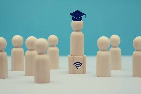 Online education. Distance learning. Internet seminar, webinar. Wooden teacher figure in cap on cube with wifi sign Stockfoto