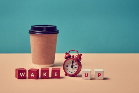 Waking up. Morning coffee. Start new day. Stop sleeping. Wake up inscription. Alarm clock, paper glass. Background