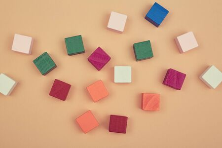 Wooden cubes mockup for creative design, copy space. Blank colourful blocks scattered on beige backdrop, place for text.