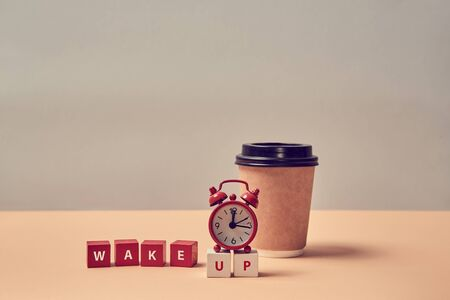 Morning coffee. Beginning new day. Awakening. Good morning. Wake up inscription. Alarm clock, paper glass. Copy space.
