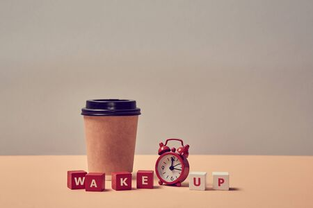 Waking up. Morning coffee. Start new day. Stop sleeping. Wake up inscription. Alarm clock, paper glass. Copy space