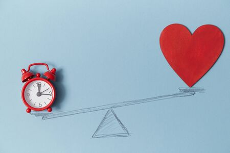 Red alarm clock and blank bright heart on scales, copy space. Love vs career mockup. Doubts of soul. Decision-making.