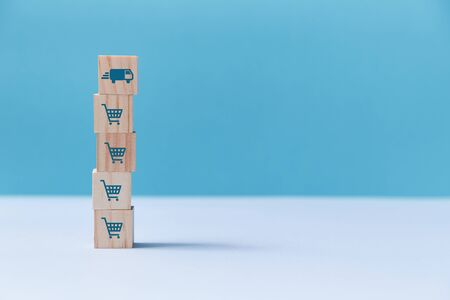 Online shopping, delivery service. On-line market. E-store, e-commerce. Stack of wooden cubes with trolley, truck signs Stok Fotoğraf