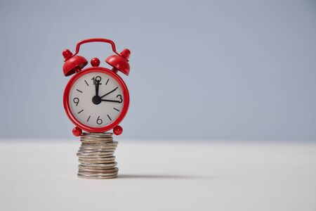 Time is money. Time-limit. Lack of time. Business deadline. Stack of coins and red alarm-clock on top, place for text Banque d'images