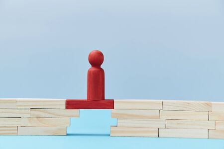 Business risk. Danger and chance. Mockup style for design. Copy space. Red wooden figures stands on plank of bridge gap.