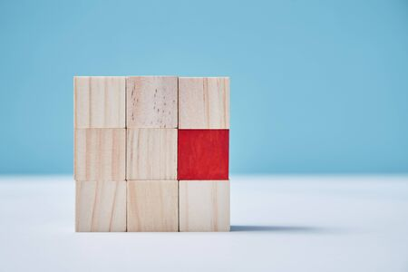 Uniqueness, originality mockup. Personal identity. Not like everyone. Square of uncolored wooden cubes, one red block