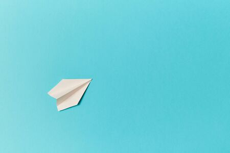 Paper white plane on blue background. Copy space. Place for text. Banco de Imagens
