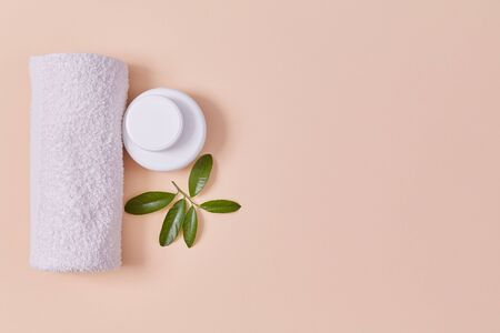 Towel and tubes with cream. Leaf as symbol for organic. Wellness and beauty concept. Copy space on pink backdrop Imagens