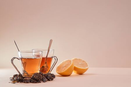 Tea ceremony. Tea party. Parts of lemon fruit and tea infusion around mugs. Copy space. Isolated on pink background