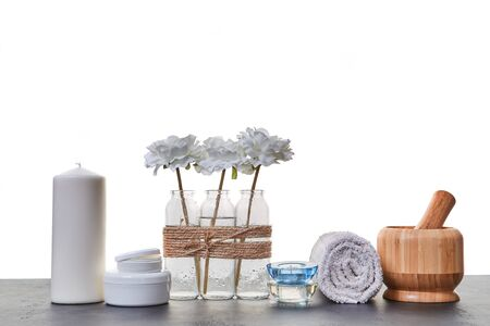 Wooden mortar tubes with cream. Candles and white towel. Aromatic oils. Spa day. Skincare. White backdrop. Copy space