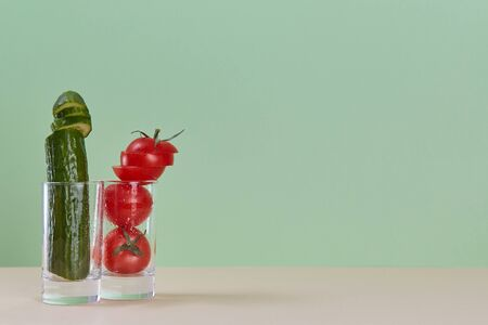 Fresh cucumber and ripe tomato in glass. Fresh juice. Healthy lifestyle concept. Copy space. Isolated on green backdrop