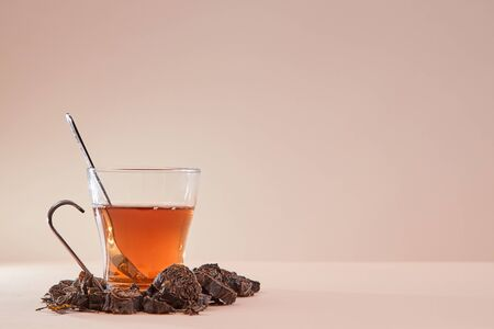 Cup made of glass filled with tea. Tea infusion around mug. Copy space. Pink background. Aromatic herbal tea concept