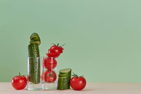 Cucumber and tomato in glass. Delicious ripe vegetable. Fresh juice. Organic food concept. Copy space on green backdrop