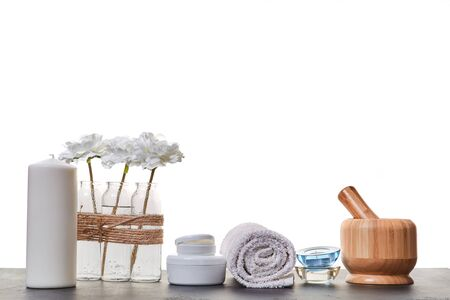 Aromatic oils. Spa day. Skincare. Wooden mortar tubes with cream. Candles and white towel. White backdrop. Copy space