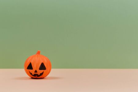 Plastic pumpkin decoration with scary face. Halloween and fall holiday concept. Copy space. Isolated on green backdrop.
