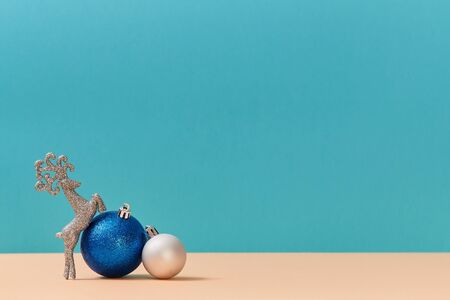 New year. Christmas holiday concept. Blue and white balls. Glitter reindeer. Copy space for text. Blue background