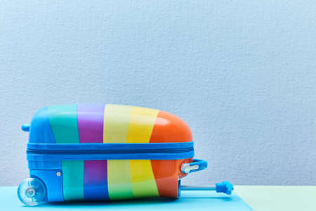 Travelling background. Summer vacation. Travelling abroad. Summer time. Bright colourful suitcase on blue, copy space Imagens